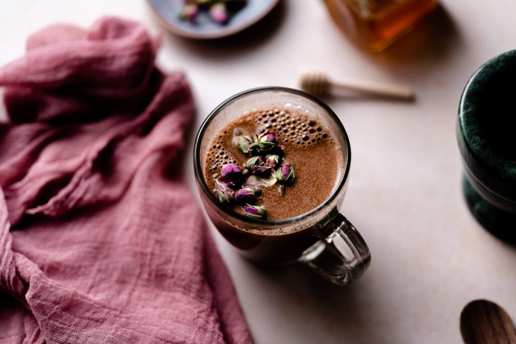 a cup of chocolate moon milk latte topped with rose buds