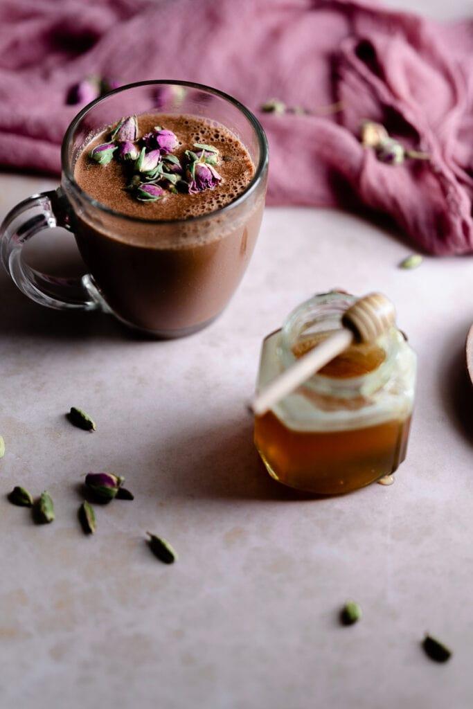 a mug of moon milk next to a jar honey