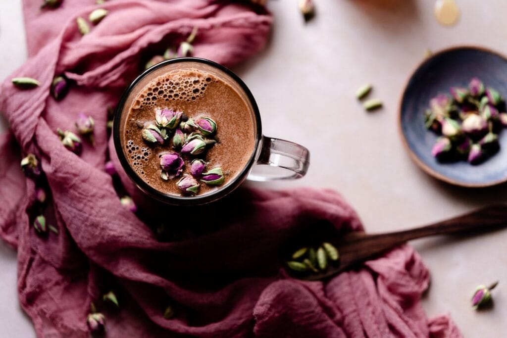 a clear mug filled with chocolate moon milk and topped with roses