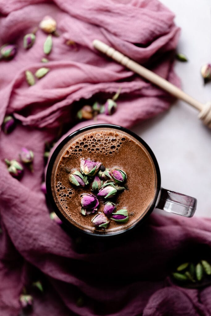 a top view of pink rose buds on a mug of rose cardamom  moon milk
