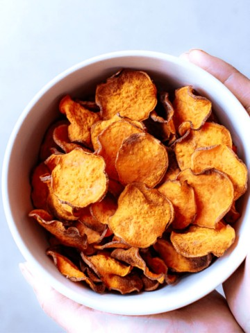 hands holding a white bowl of crispy air fryer sweet potato chips