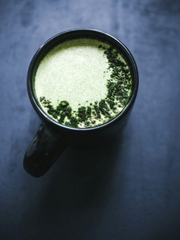 a black mug filled with green moon milk