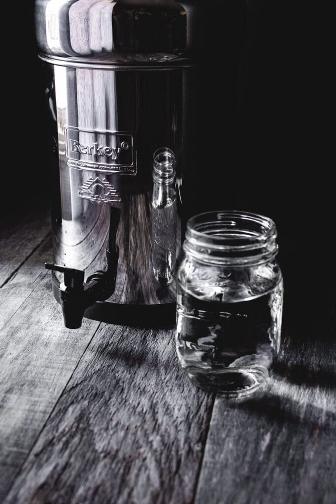 stainless steel berkey water filter system resting on wooden table next to backlit glass of water