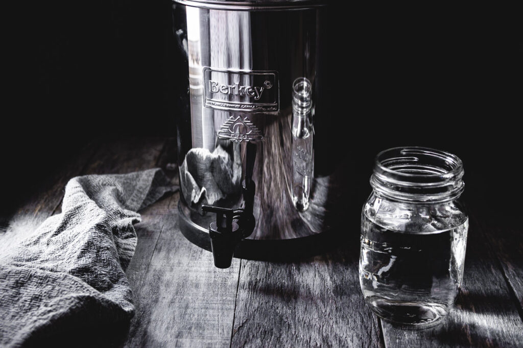 travel berkey water filter system on wooden table with a glass of water backlit