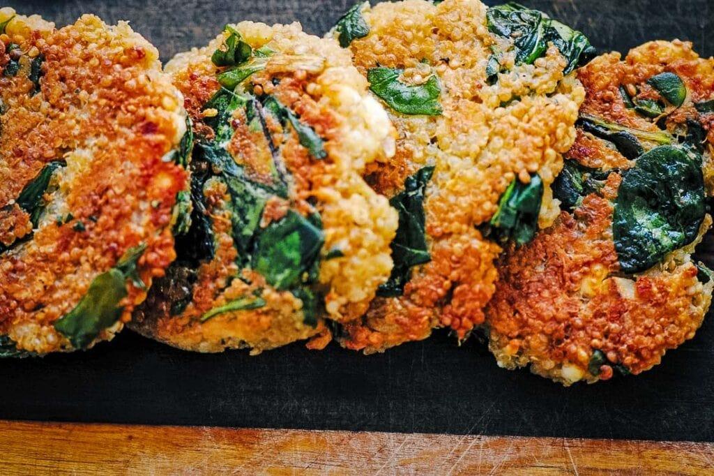 crispy quinoa cakes spread out on dark cutting board