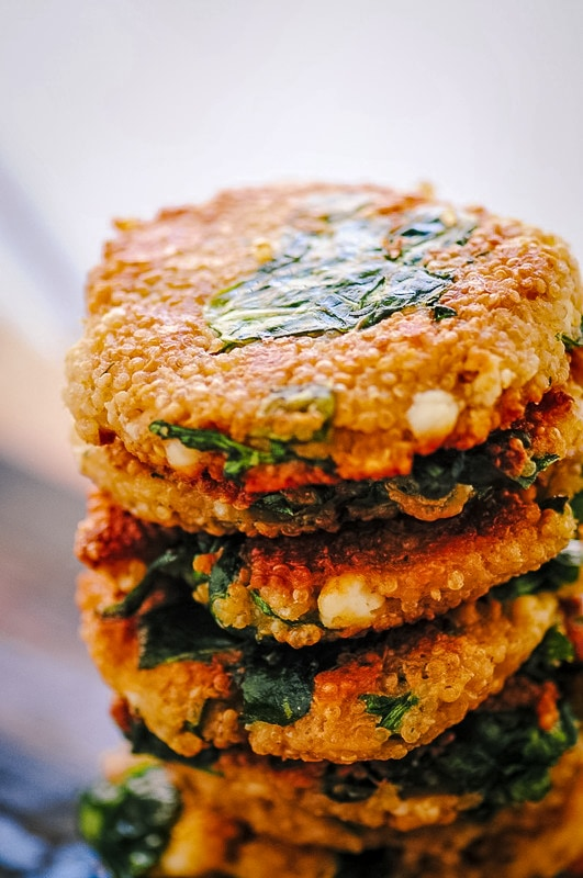 a stack of feta quinoa cakes with greens