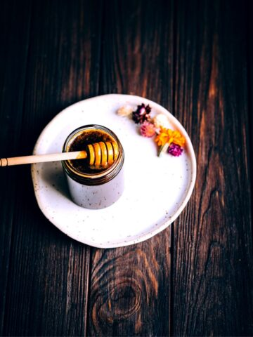 an open jar of golden vegan honey resting on a white plate