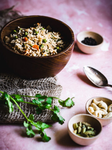 vegan biryani web story cover a teak wooden bowl filled with indian inspired rice dish