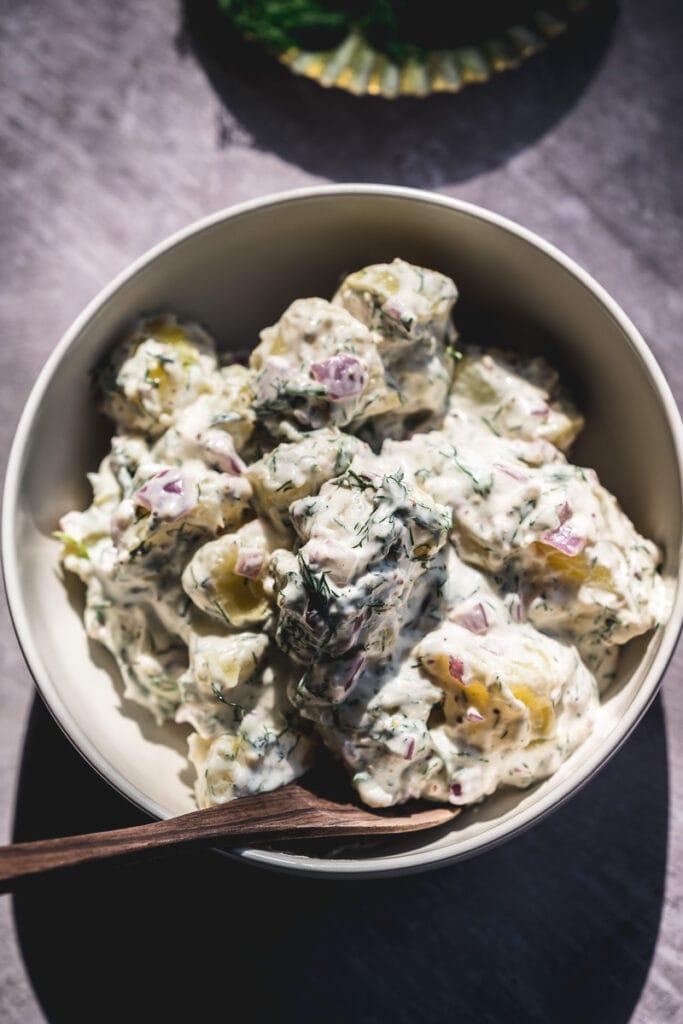 a mound of creamy vegan potato salad rests in a white ceramic bowl