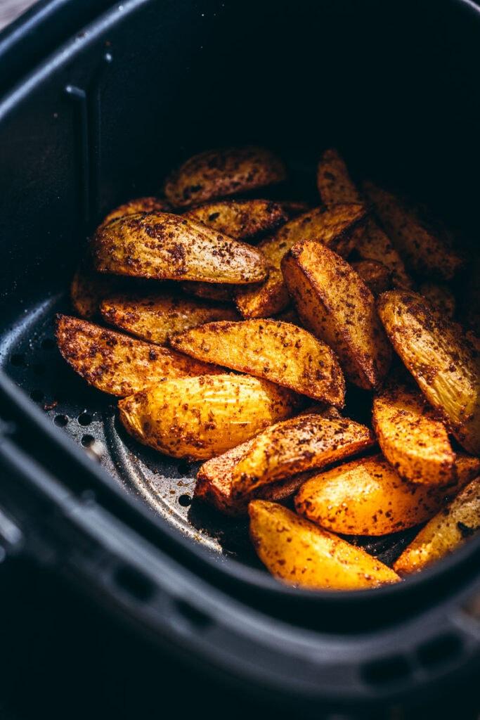 a shot of air fryer potato wedges sitting in a black air fryer basket lit by golden light