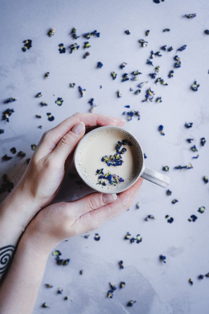 hands holding a white mug filled with moon milk with dried violet flowers scattered about