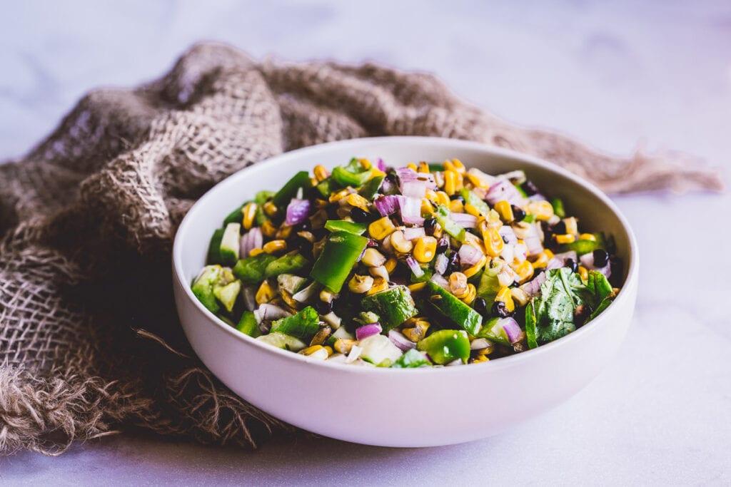 a large white ceramic bowl filled a rainbow corn salad