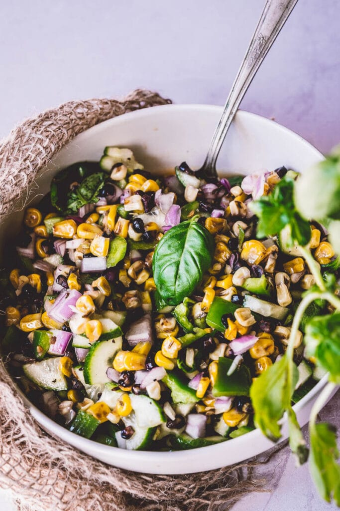burlap surrounds a white ceramic bowl filled with stovetop grilled corn salad