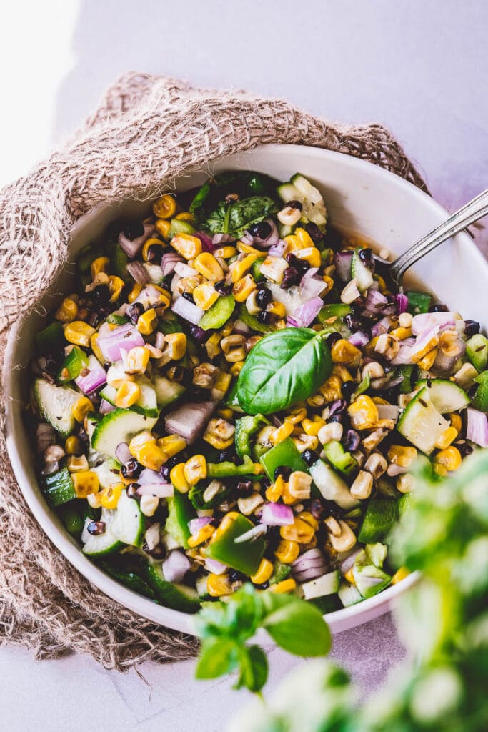 vegan grilled corn salad topped with fresh basil
