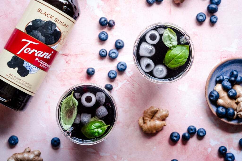 glasses of iced blueberry ginger tea refreshers next to a bottle of torani syrup