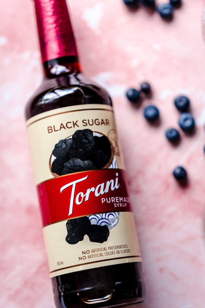 a tall torani puremade black sugar syrup container on a pink backdrop