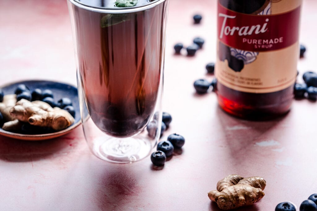 a side angle shot of a tall clear glass tumbler filled with blueberry ginger tea made with ice and torani black sugar syrup