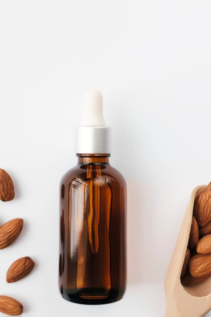 an amber glass bottle filled with almond extract surround by scattered raw almonds