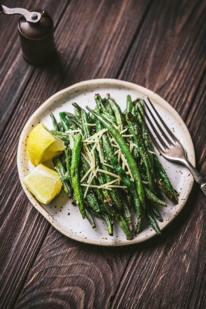 crispy air fryer green beans garnished with lemon wedges and parmesan cheese