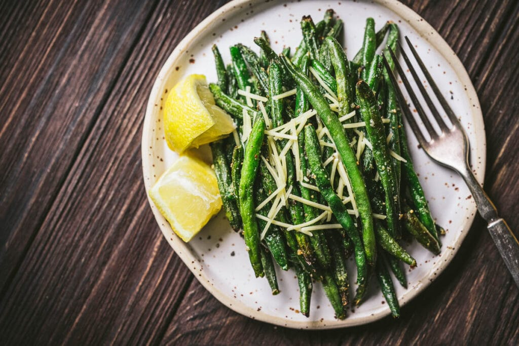 a speckled white matter ceramic plate topped with crispy air fryer green beans garnished with parmesan and lemon juice