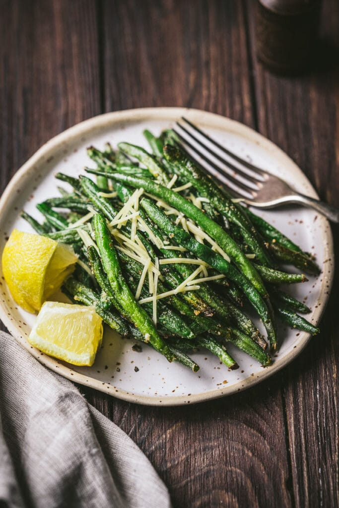 a plate filled with air fryer french green beans lemon wedges and shredded parmesan cheese