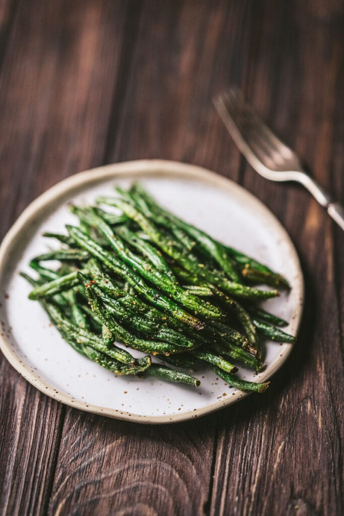 a ceramic plate topped with crispy air fryer frozen green beans