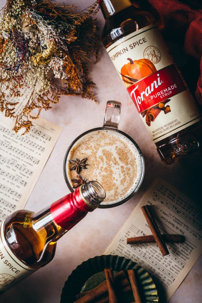 a bottle of torani pumpkin spice syrup being poured into a mug of pumpkin spice steamer