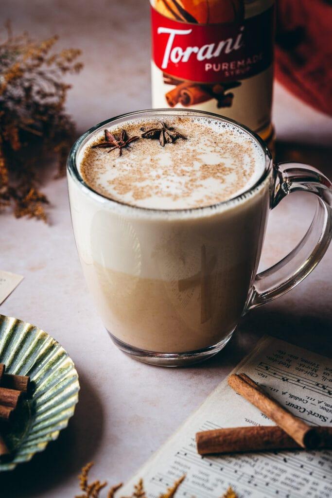 a tall clear glass mug filled with oat milk pumpkin spice steamer