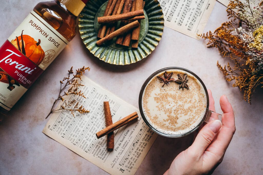 a hand holding a glass mug of pumpkin spice steamer topped with star anise